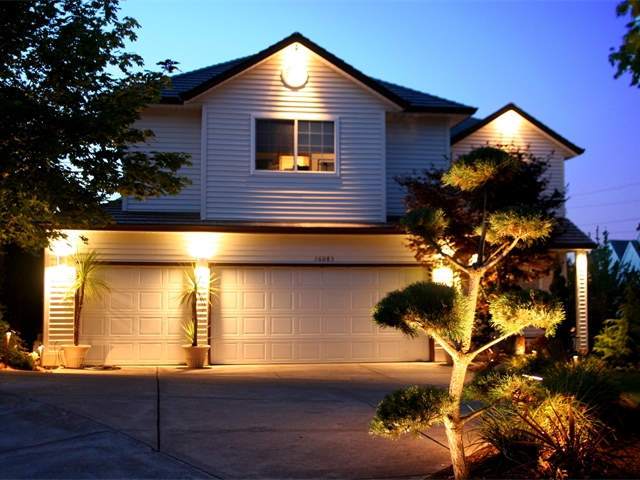 Here we installed Light Fixtures at the Peaks of this Beaverton Home, Along the Columns by the Garage & Uplighting on the Trees within the Landscape