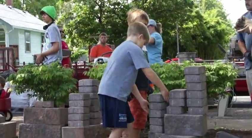 Other volunteers bring pavers over to installers