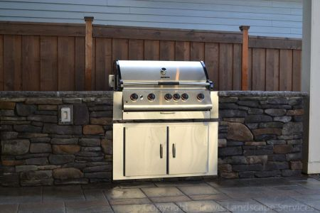 Outdoor Kitchen with Stone Countertops, SS Doors, Stone Siding