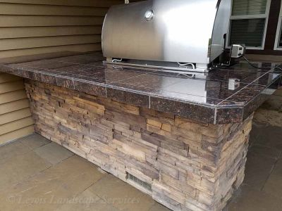 Outdoor Kitchen with Granite Tile Countertops, Stone Siding, BBQ